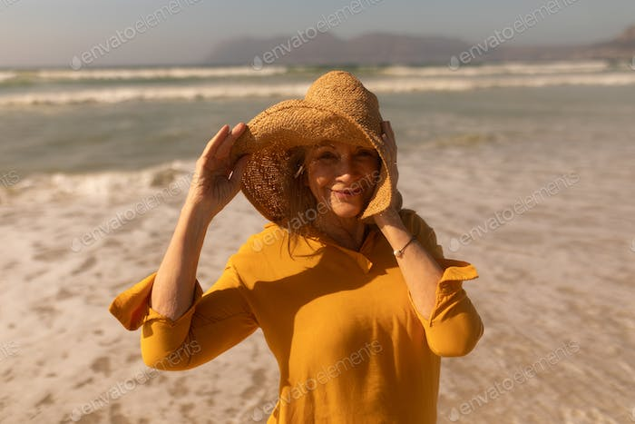Portrait of active senior woman in hat standing on the beach