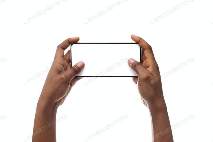 Female hands holding smartphone with blank screen, playing video games