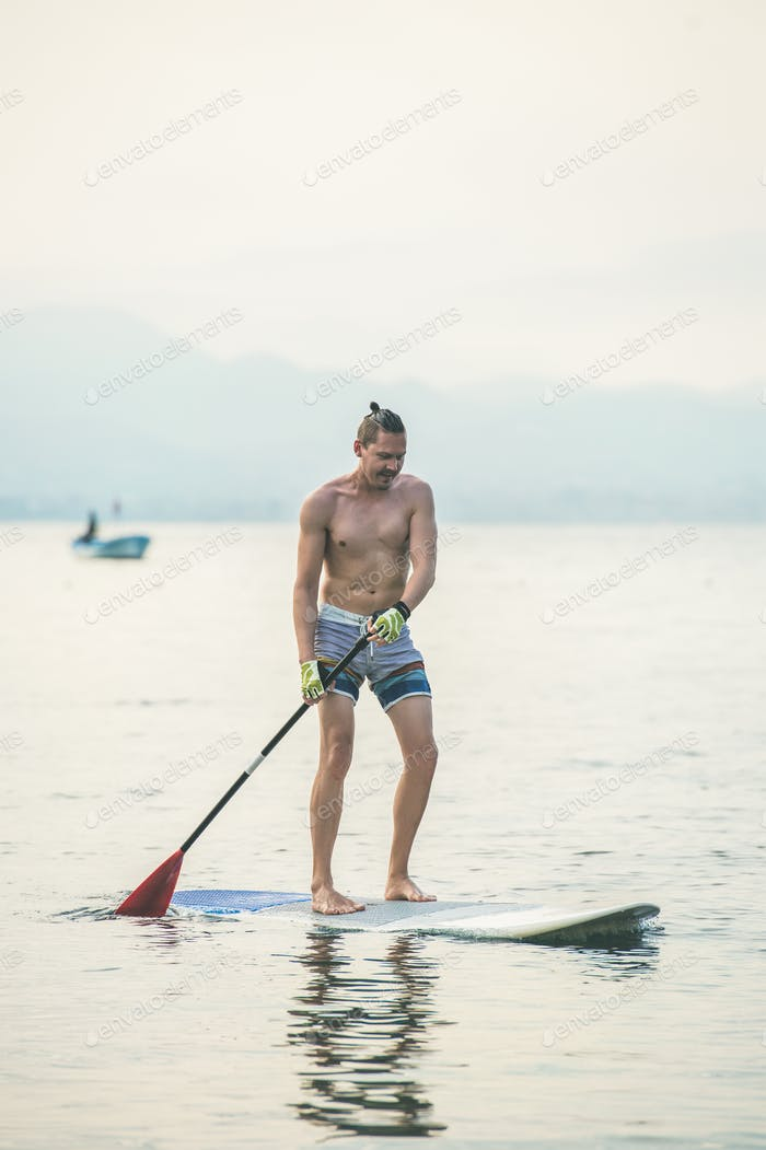 Young european man tourist practicing paddle boarding