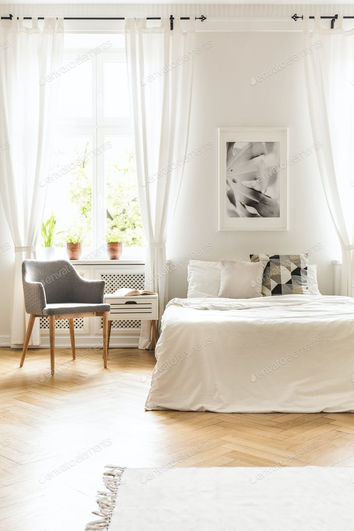 Grey armchair at window with drapes in white bedroom interior wi