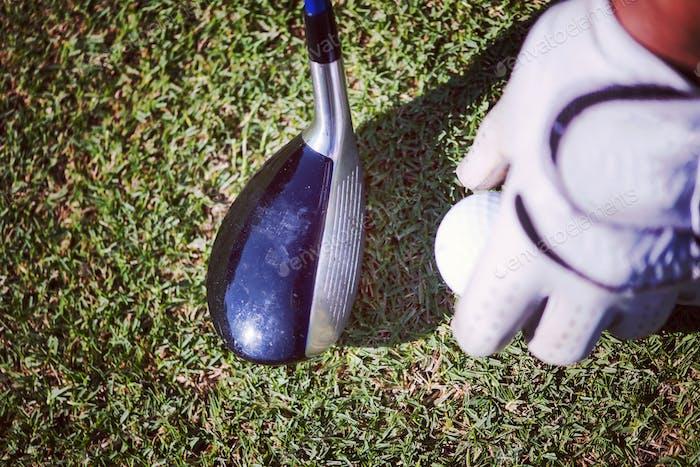 Golfschläger und Ball im Gras