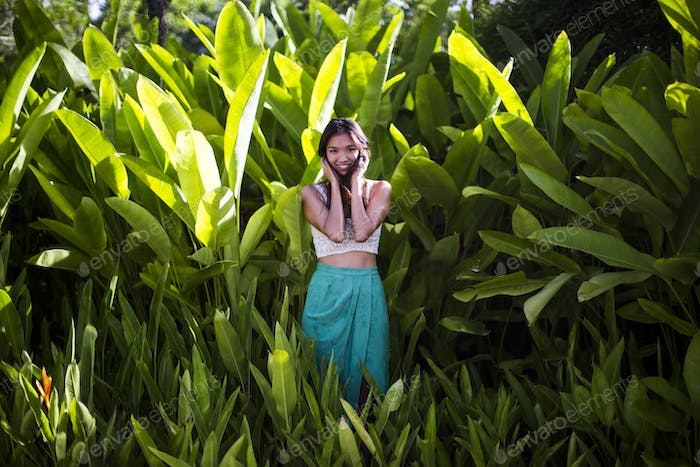 Young woman standing in rain forest with lush green foliage.