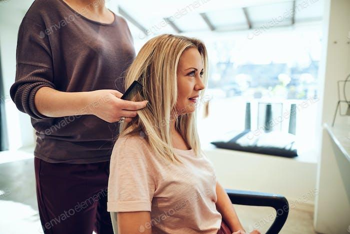 Smiling woman having her hair cut in a beauty salon
