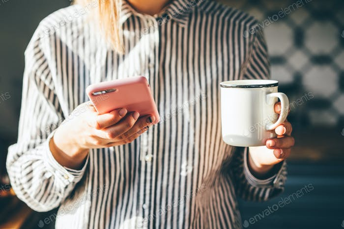 Woman holds a cup of coffee and reading news on phone at the morning.