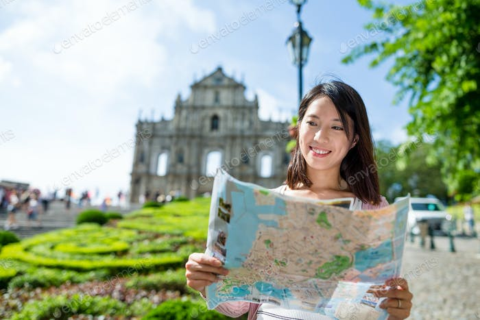 Woman looking for location on city map