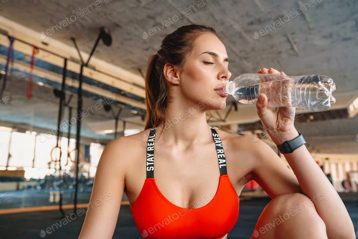 Attractive healthy young sportswoman drinking water