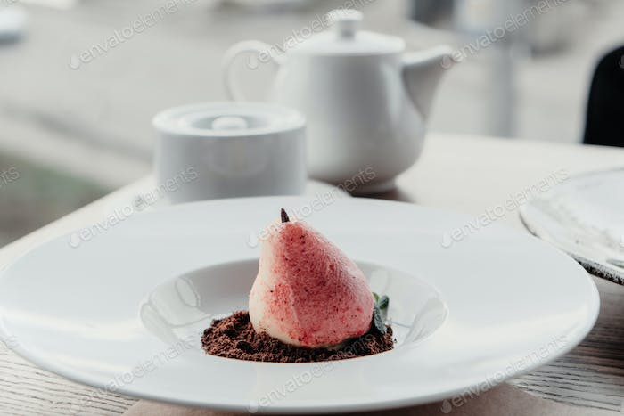 Williams pear shaped mousse glazed dessert on the white plate. Delicious dessert for holiday