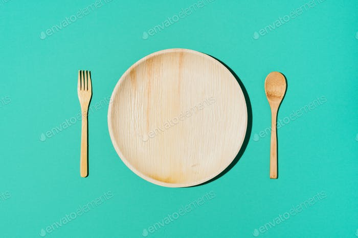 Disposable tableware from natural materials, wooden spoon, fork on yellow background. Eco-friendly