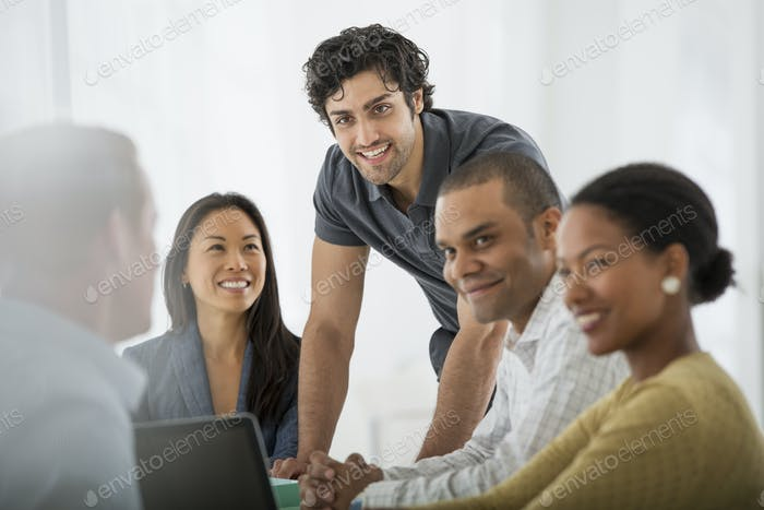 Ein Büro in der Stadt. Geschäft. Eine multiethnische Gruppe von Menschen um einen Tisch.