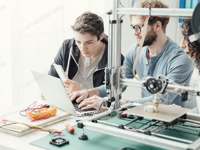 Group of students using a 3D printer and a laptop