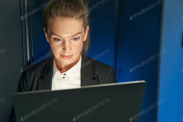 Female technician using laptop to analyze server