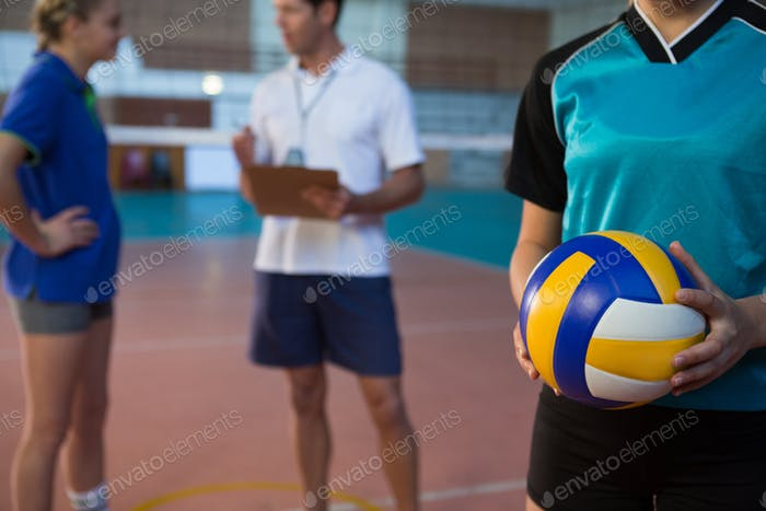 Volleyball player holding ball in court