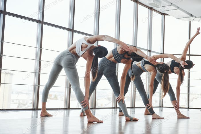 Pilates and fitness. Group of sportive girls in a spacious gym with big windows have training