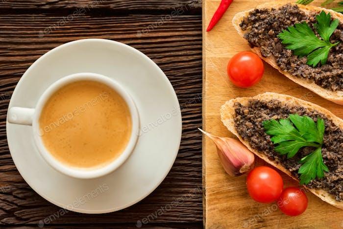 Frische leckere Bruschetta mit Trüffelsauce, Petersilie, Tomaten und Tasse Kaffee