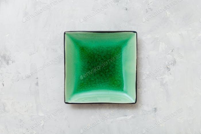 obige Ansicht von grünen quadratischen Untertasse auf grauem Beton