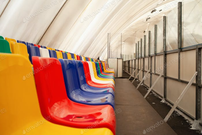 Multi-colored seats. ice rink. Sports stadium, stands for fans