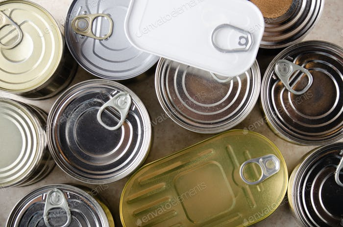 Flacher Blick auf verschiedene Konserven in Blechdosen auf Küchentisch