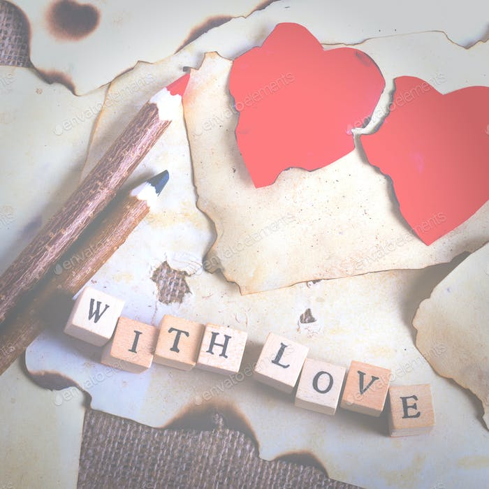 Old vintage sheet of paper, two red hearts, wooden pencils and words With love on cubes on burlap