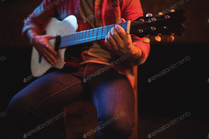 Mid-section of man playing guitar