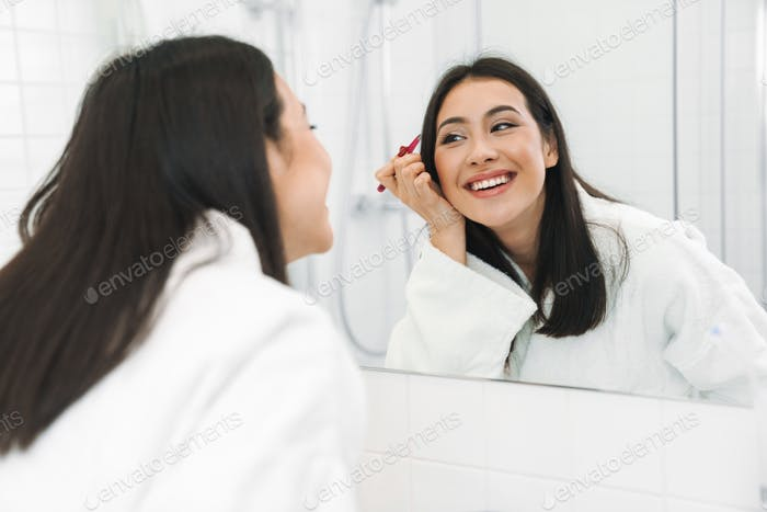Positive young woman correcting brows.