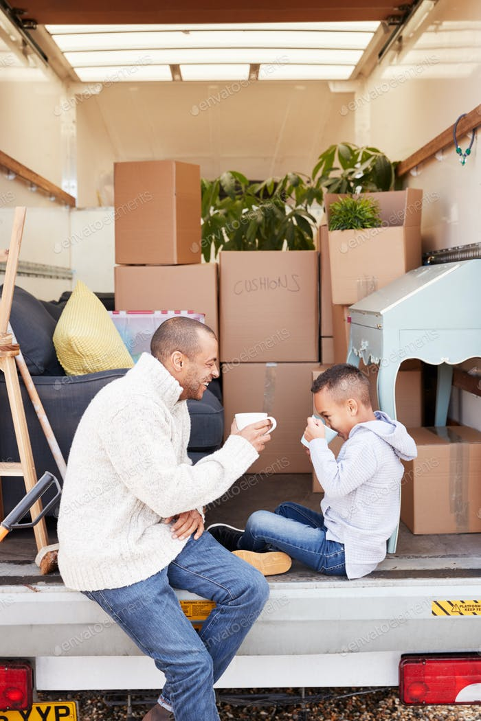 Father And Son Sitting On Tailgate Of Removal Truck Having Drink On Moving Day