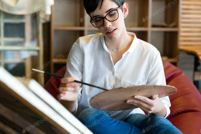 Creative pensive art school painter working on painting