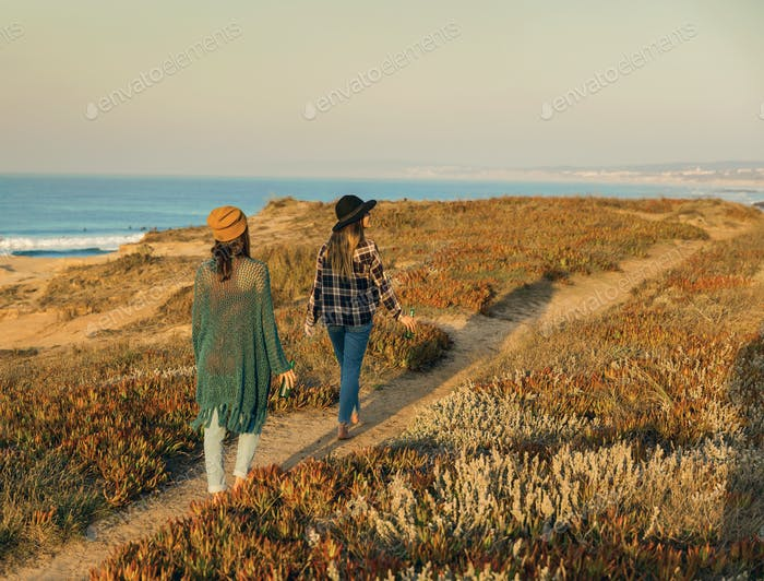 Girs walking ove the coastline