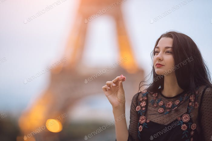 Paris woman smiling eating the french pastry macaron in Paris against Eiffel tower