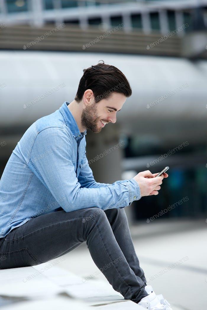 Man sending text message on cellphone