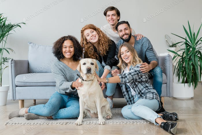 Cheerful young friendly companions and their cute pet relaxing at home