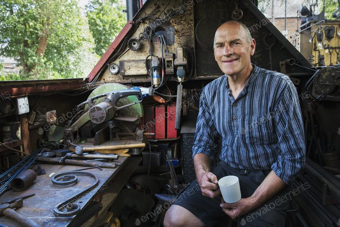 Blacksmith sitting on a working boat, a narrowboat on a waterway, holding a mug, smiling at camera.