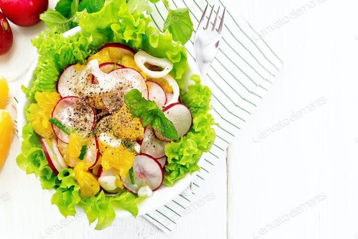 Salad of radish and orange with mint on light board top