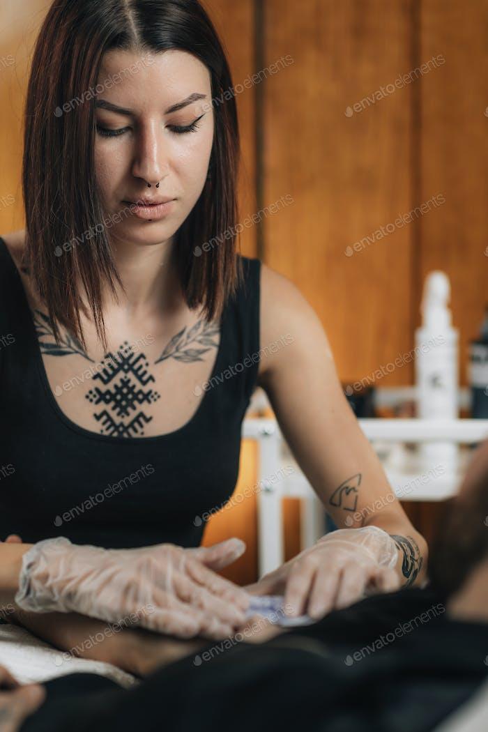 Tattooing.  Female Tattoo Artist Applying Tattoo Stencil onto Male Arm before Tattooing
