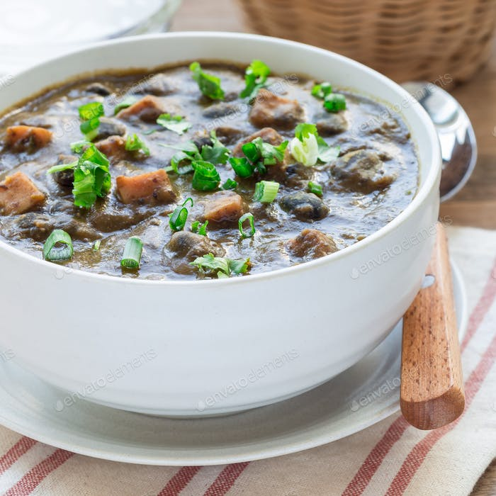 Homemade black bean and ham soup in ceramic bowl on wooden table, square format