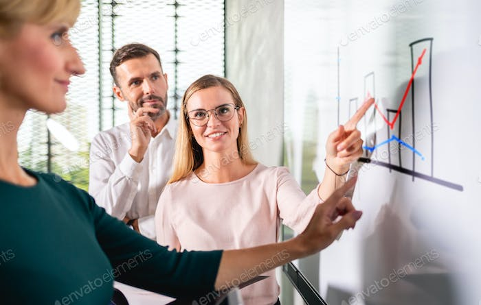 Business people in front of white board gives presentation report at conference room