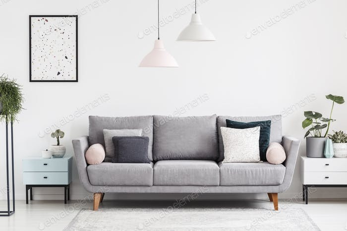 Grey sofa with pillows in white apartment interior with poster a