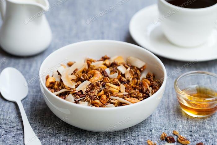 Gesundes Frühstück. Frisches Müsli, Müsli mit Kokosnuss, Banane und Nüssen in einer weißen Schüssel.