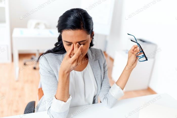 businesswoman rubbing tired eyes at office