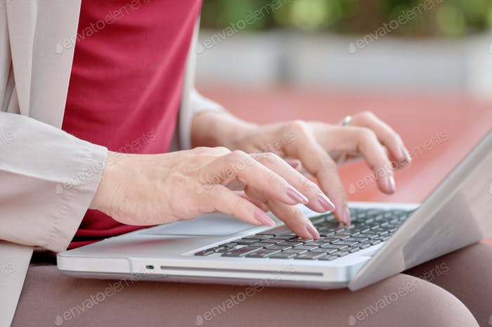 Woman typing on keyboard of computer laptop