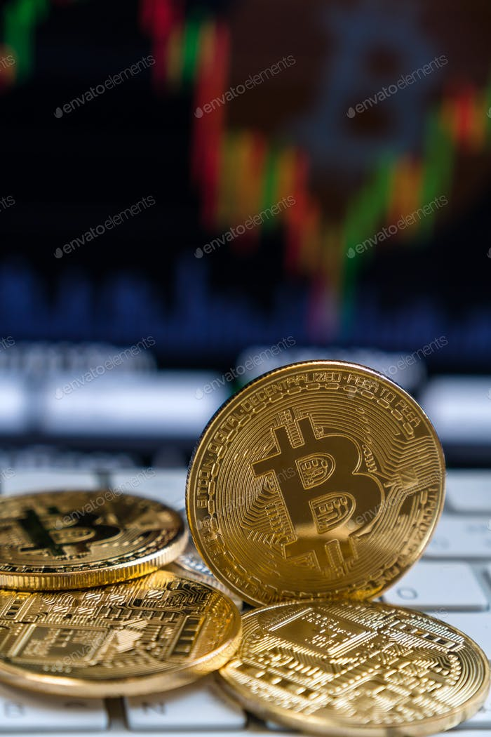 Closeup Bitcoins mockup on the keyboard over the cryptocurrency trading graph