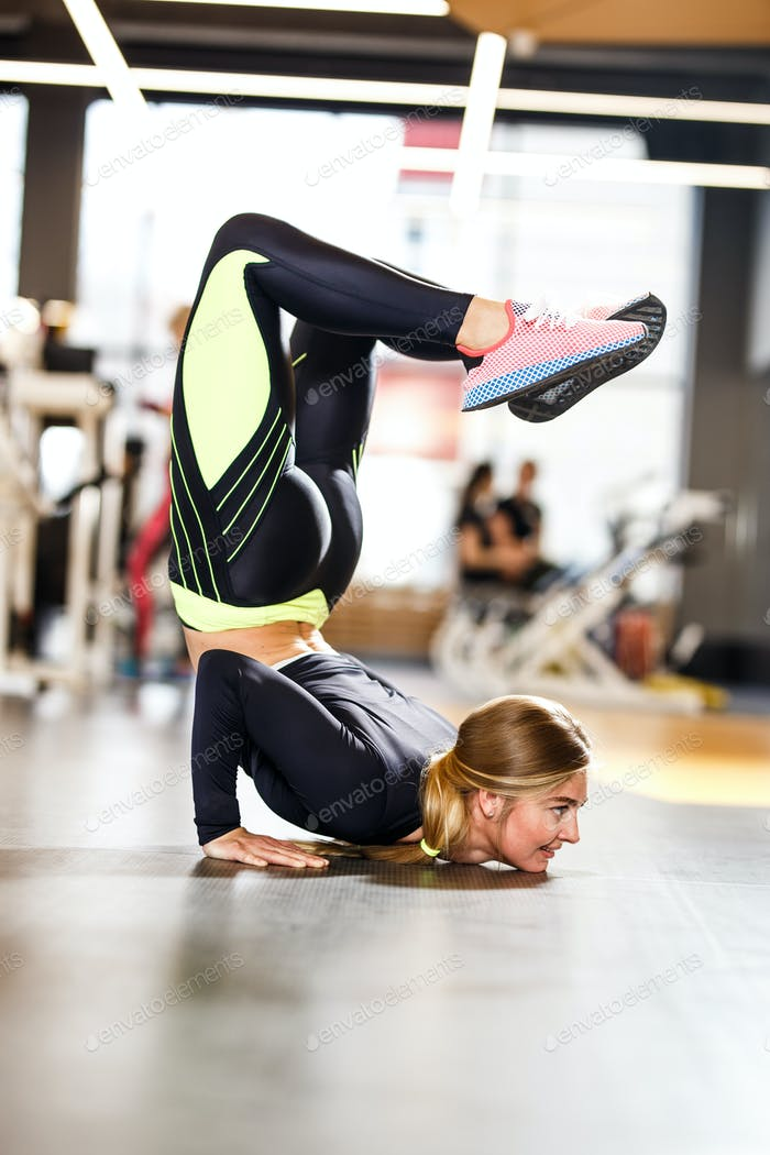 Young athletic girl dressed in sportswear doing handstand on the floor in the modern gym