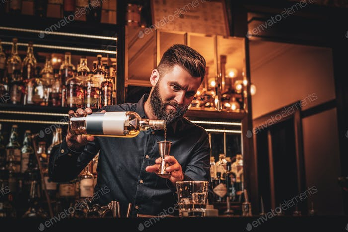 Bar manager is making drinks at the bar