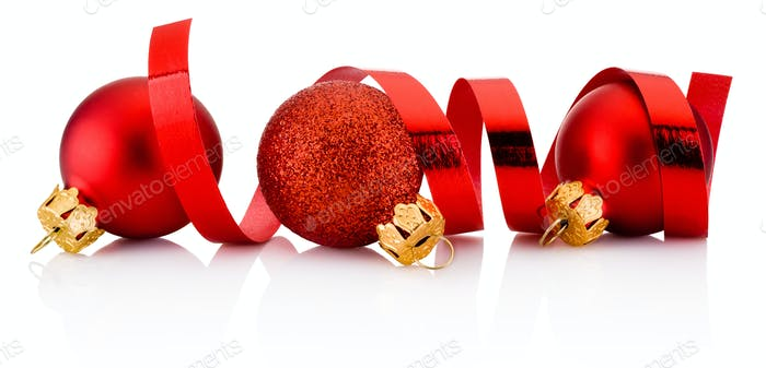 Three red Christmas baubles and curling paper isolated on white