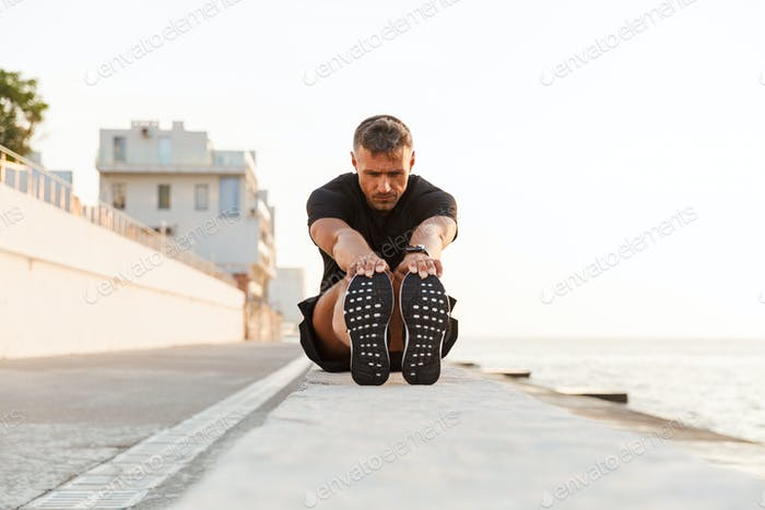 Image of caucasian sportsman 30s in tracksuit sitting on parapet