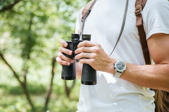 Man with backpack and binoculars in forest