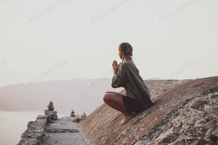 Woman sitting and meditating on stones in Monolithos, Rhodes, Greece