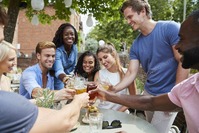 Friends Sitting At Table In Pub Garden Making Toast Together