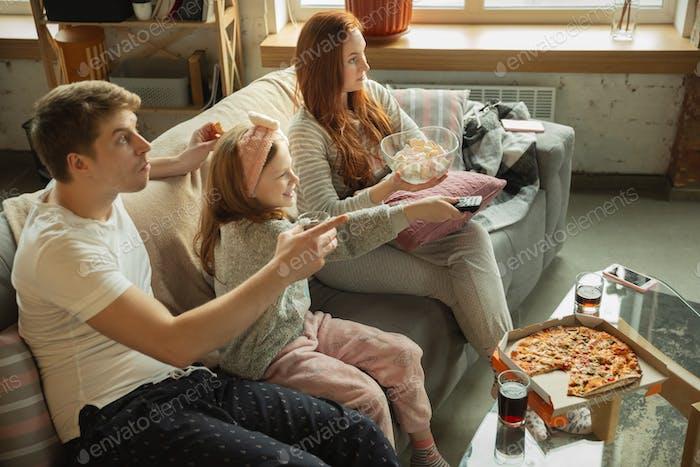 Familie verbringen schöne Zeit zusammen zu Hause, sieht glücklich und fröhlich, Essen Pizza