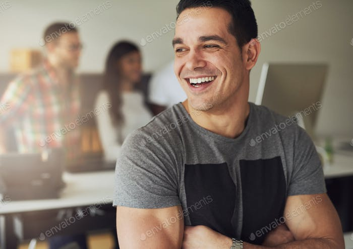 Cheerful creative businessman standing with arms crossed