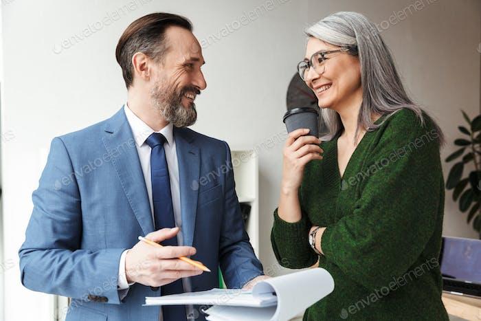 Foto von lächelnden Kollegen, die Kaffee trinken, während sie mit Dokumenten arbeiten